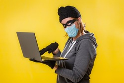A hacker in a medical mask is holding a laptop. Yellow background. The concept of cybercrime growth in the context of the coronavirus crisis