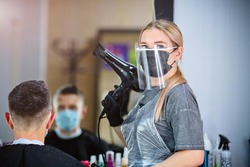 A hairdresser with security measures for Covid-19 holding a hairdryer and looking at the camera in a medicine mask, social distance, cutting hair with a medical mask, eye mask and rubber gloves