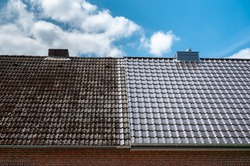 A half cleaned house roof shows the before and after effect of a roof cleaning.