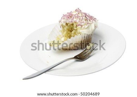 A half eaten homemade cupcake on a white plate with a dessert fork.  Isolated on a white background with an accurate clipping path.