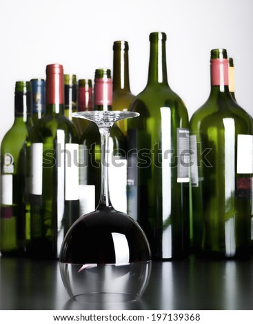 A half-full, upside down wine glass in front of several empty wine bottles.