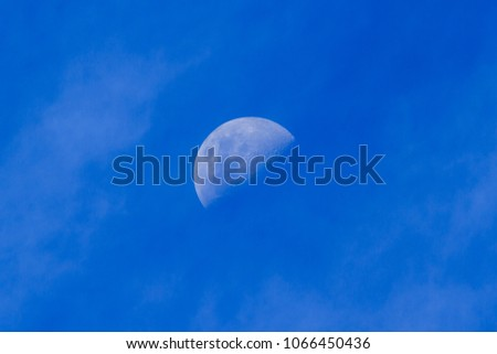 A Half Moon (First Quarter, Southern Hemisphere) Seen in the Daytime, In a Blue Sky With Wispy Clouds
