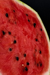 A half of fresh watermelon isolated on black background.