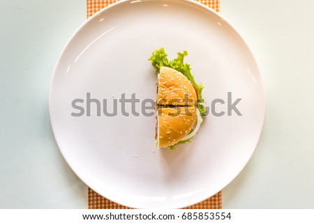 a half of hamburger on a white ceramic plate and table background. Top view.