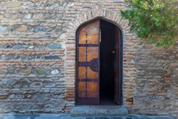 A half open wooden door of the church against the backdrop of a stone wall. Wooden doors of the church.