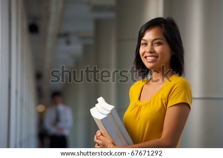 A half portrait of a cute smiling college student on a beautiful modern campus.  Young female Asian Thai model late teens, early 20s of Chinese descent.