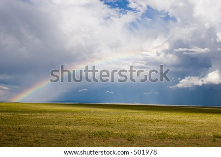 A half-rainbow reaches into the clouds at the edge of a storm over the plains of northern New Mexico