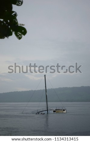 A half submerged yacht is in a bay. The sky is overcast and the water is grey. The heads of some children can be seeh as they swim near the boat. A forest covered hill is in the background. #1134313415