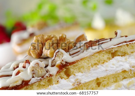 A half walnut on a walnut cake with strawberries and other cakes in the background (Selective Focus, Focus on the front of the walnut)