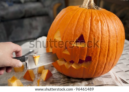 A Halloween jack o' lantern being carved for Halloween.