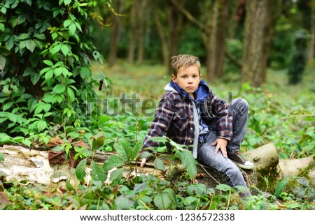 A halt in the woods. Small boy halt and relax sitting on tree in forest. Small boy resting on nature. You cant halt time.