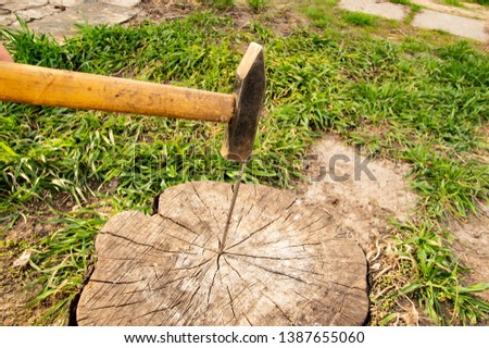 A hammer hammers a nail into a stump - a working tool #1387655060