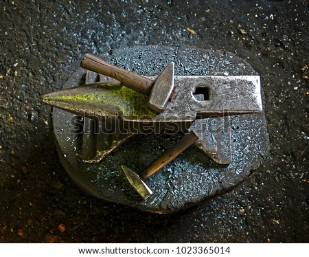 A hammer on an anvil. The tool  uses a blacksmith in a blacksmith shop
