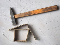 A hammer over a cardboard house - an association of misfortune, destruction of a house under the blows of fate