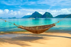 A hammock at the beach with the view of Bacuit Archipelago islands (El Nido, Philippines)