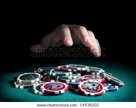 A hand about to rake a big pile of chips.