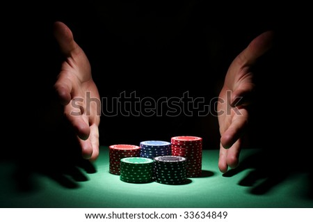 A hand about to rake a big pile of chips. - stock photo