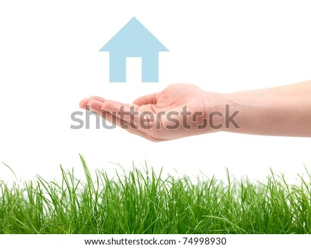 A hand and house over green grass isolated against a white background
