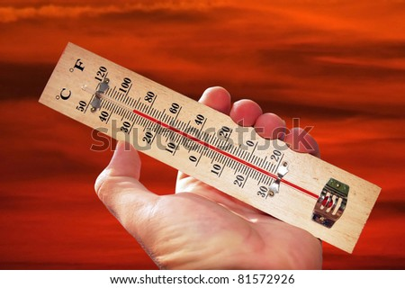 A hand and temperature scale over a red sky shows high temperatures during a heat wave. Concept photo of heat wave , warm weather, global warming, high temperatures, climate change.