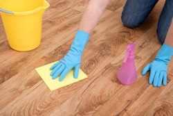 A hand cleaning a parquet floor