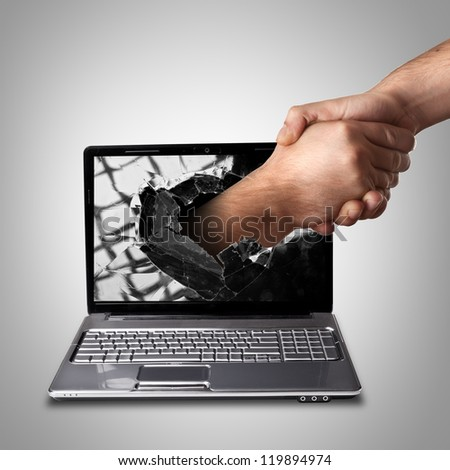 A hand comes right out of the laptop screen to shake hands CONCEPT. High resolution