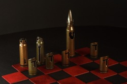 A hand-crafted chess pieces made of bullet shells (7.62x54 mm and 7.62x39 mm caliber). Chess game. Dark background. The small depth of field