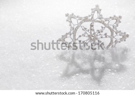 A hand-crafted fabric snowflake on a fresh snow