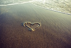 A hand drawn heart on a sand about to be wiped away with tidal waves foam. the symbol of fast love and infatuation passing away.  Breaking up. Fading of fragile affection and romantic relationships.