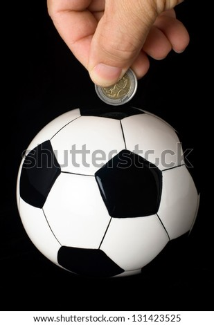 A hand drops a coin into a piggy bank in the shape of a soccer ball.