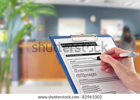 A Hand filling in medical information form with blurred hospital reception area in background
