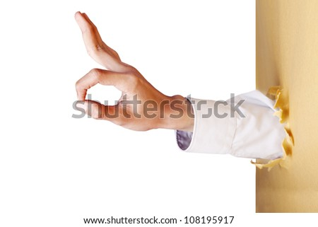 A hand gesture giving ok signal breaking through a paper wall