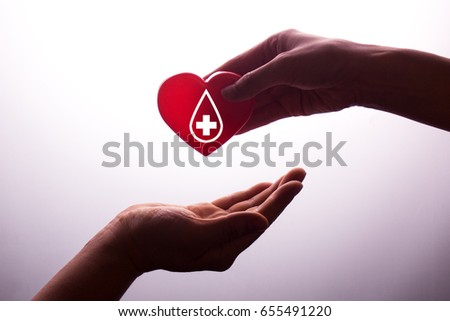 A hand gives a red heart to a hand - blood donation,world blood donor day #655491220
