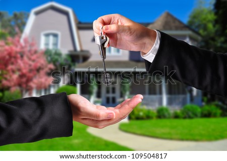 A hand giving a key to another hand. Both persons in suits and a house in the background.
