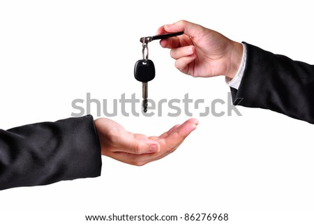 A hand giving a key to another hand. Both persons in suits. Isolated.