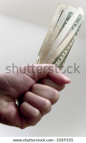 A hand grabbing a fistful of US twenty dollar bills