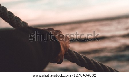 A Hand Grabbing a Rope Strongly with the Sea in the Background #1270494082