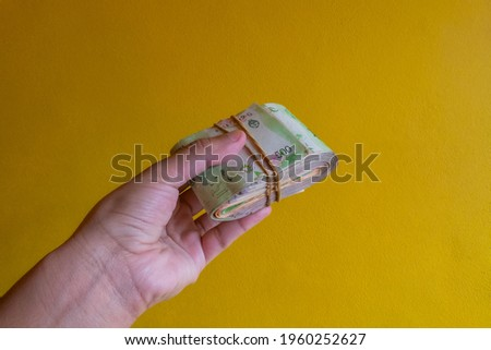 a hand grabbing a wad of Argentine bills with an elastic band and a five hundred bill at first sight Photo stock ©