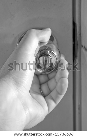 A hand grasping a shiny doorknob in black and white.
