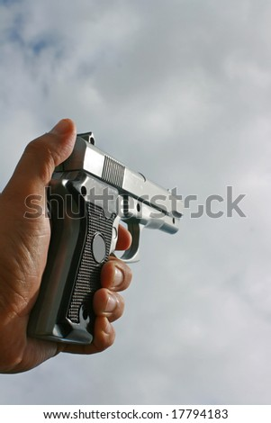 A hand gun held in the hand held against a sky backdrop