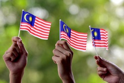 a hand hold malaysia flag. All over Malaysia will be flagged for the celebration of independence day in month of august.