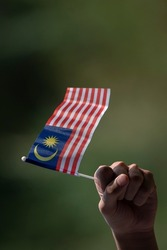 a hand hold malaysia flag. All over Malaysia will be flagged for the celebration of independence day in month of august. soft and grain image.