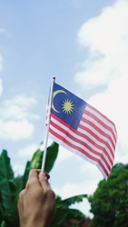 a hand hold Malaysia National flag . Independence day concept .