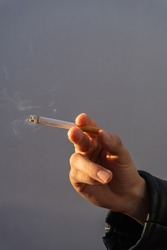 a hand holding a cigarette in the sunset. holding a lit cigarette with hand at golden hour. artistic photo of lit cigarette held by a hand, close up hand may 31 or world anti-smoking day.