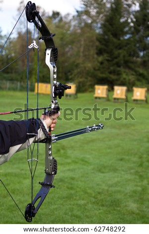 a hand holding a compound bow