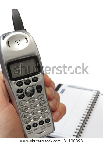 A hand holding a cordless phone, with the display facing the camera, and a blurred blank telephone directory in the background, isolated on white.