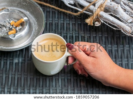 a hand holding a cup of black coffee and cigarette smoking on the table  relaxing time bad habits lifestyle, unhealthy lifestyle Photo stock ©