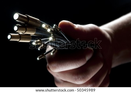 a hand holding a fibre optic on black background