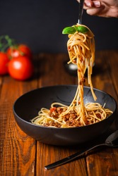 A hand holding a fork with spaghetti with bolognese tomato sauce in black bowl on wooden table