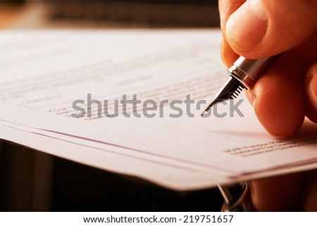 A hand holding a fountain pen and about to sign a letter. Styling and small amount of grain applied. #219751657