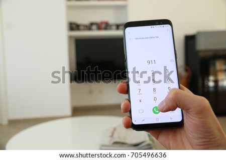 A hand holding a generic new mobile phone which displays the emergency number 911 on the touch screen. A concept about calling for help from inside a house. An image on an interior background.